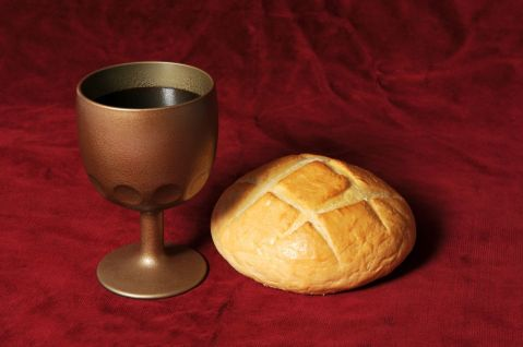 Communion-elements-represented-by-bread-and-wine-over-a-red-background